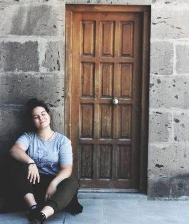 26.07.19. Ahşap kapı önünde oturan kız. KARS